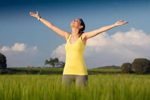 giovane donna godendo la primavera in piedi in un campo di cereali foto