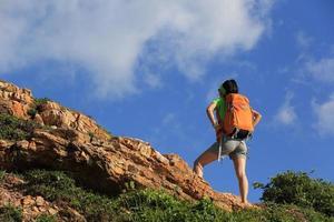 il viaggiatore con zaino e sacco a pelo incoraggiante della giovane donna gode della vista al picco di montagna foto