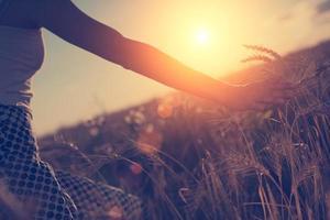 picchi di grano commoventi della mano della ragazza foto