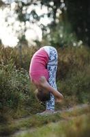giovane donna flessibile che piega il doppio foto