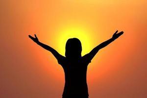la siluetta della giovane donna sul tramonto concepft per successo si rilassa foto