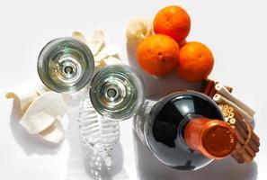 bottiglia di vino con bicchieri e arance siciliane foto