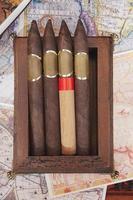 quattro sigari in una scatola su uno sfondo colorato foto