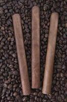 tre sigari su sfondo di chicchi di caffè foto