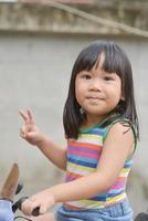 la ragazza asiatica sveglia gode del gioco dell'automobile foto