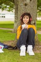 donna rilassata che gode della musica nel parco foto