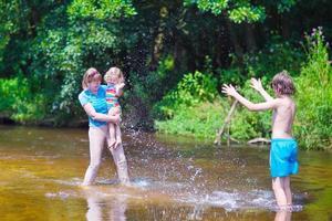 famiglia che gode della giornata calda su un fiume foto