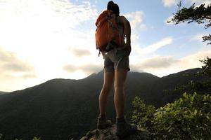 il viaggiatore con zaino e sacco a pelo della donna sul picco di montagna gode della vista foto