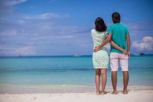 giovani coppie che si godono sulla spiaggia di sabbia bianca foto