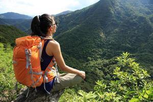 il viaggiatore con zaino e sacco a pelo della donna gode della vista alla scogliera del picco di montagna foto