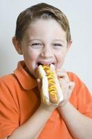 giovane ragazzo che tiene mangiare hot dog foto