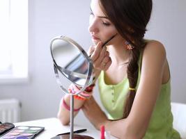 giovane bella donna che fa trucco vicino allo specchio foto