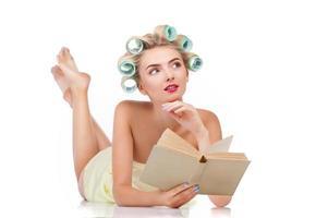 attraente casalinga giovane sta leggendo qualcosa di interessante foto