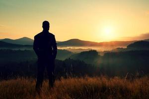 escursionista stare sul prato con steli d'oro di erba foto