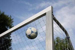 pallone da calcio che vola in un obiettivo foto