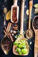 cucchiai di legno con spezie ed erbe aromatiche foto