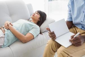 terapeuta ascoltando il suo collega e prendendo appunti foto
