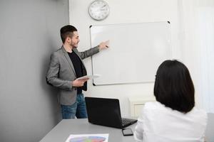 giovane uomo d'affari o insegnante che mostra i dati sul bordo bianco foto