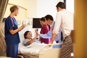 riunione del gruppo di medici intorno al paziente femminile nella stanza di ospedale foto