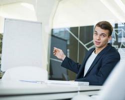 Ritratto di giovane uomo d'affari che dà presentazione al tavolo della conferenza foto