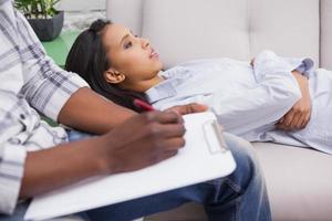 donna preoccupata sdraiata sul divano mentre la scrittura di psicologo foto