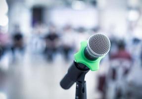 stretta di microfono nella sala conferenze su sfondo sfocato