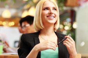 donna di affari allegra che osserva in su in ufficio foto