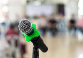 stretta di microfono nella sala conferenze su sfondo sfocato foto