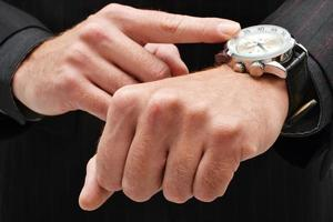 uomo d'affari che punta a un orologio foto