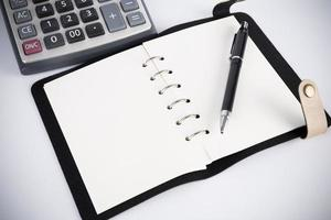calcolatrice e penna sul taccuino in bianco foto