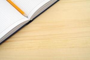diario e matita sul tavolo di legno con spazio di testo libero.