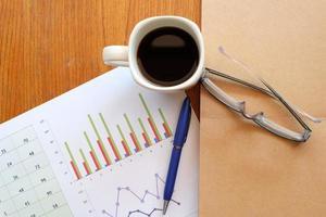 taccuino e grafico sulla tavola di legno con caffè foto