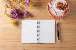 taccuino con penna sul tavolo di legno foto