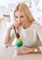 ragazza bere cocktail tropicale brillante foto