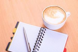 Apra il taccuino in bianco con la tazza di caffè sul tavolo foto