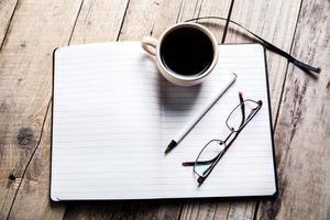 occhiali su notebook con penna e tazza di caffè foto