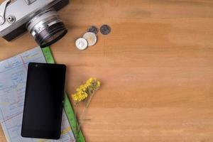 macchina fotografica d'epoca, monete, mappa, fiori gialli e cellulare su legno foto