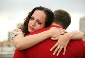 primo piano della donna che abbraccia uomo e piangere con il trucco in esecuzione foto