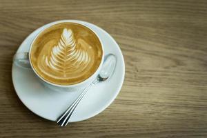 caffè caldo del latte di arte in una tazza sulla tavola di legno foto