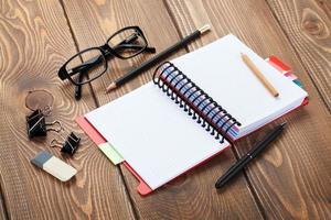 tavolo da ufficio con blocco note, matite colorate e forniture foto