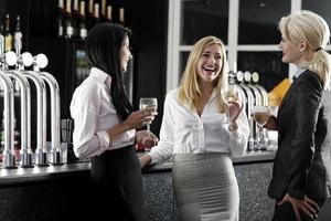 donne che si godono un bicchiere di vino foto