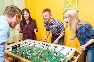 amici felici giocando a hockey da tavolo foto