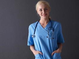 giovane donna medico con stetoscopio isolato su grigio foto