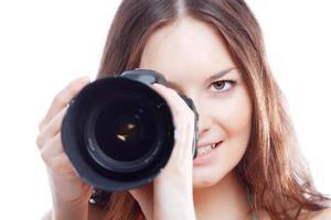 donna sorridente con fotocamera professionale
