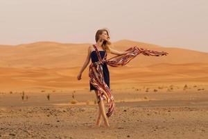 bella donna nel deserto con sciarpa foto