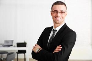 uomo d'affari in piedi con le braccia conserte foto