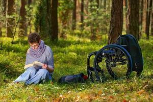 donna disabile che legge un libro nella foresta, sedia a rotelle foto