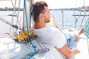 uomo simpatico sdraiato sul ponte dello yacht foto