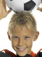 ragazzo (10-11) con pallone da calcio, primo piano foto