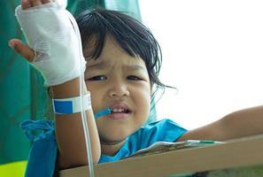 bambini asiatici di malattia si siedono su una sedia in ospedale